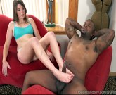 Sexy redhead strokes his big black cock with her feet